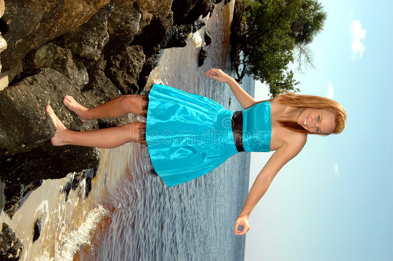 Playful teen on rocks. A teen in her prom dress walking on the rocks at the beach stock photo