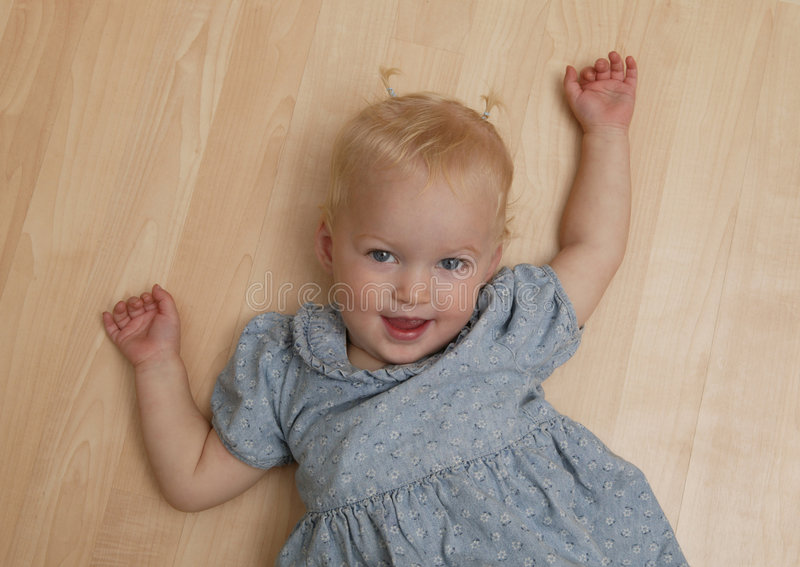 Playful Toddler. Playful little girl on the floor, looking at parent stock photo