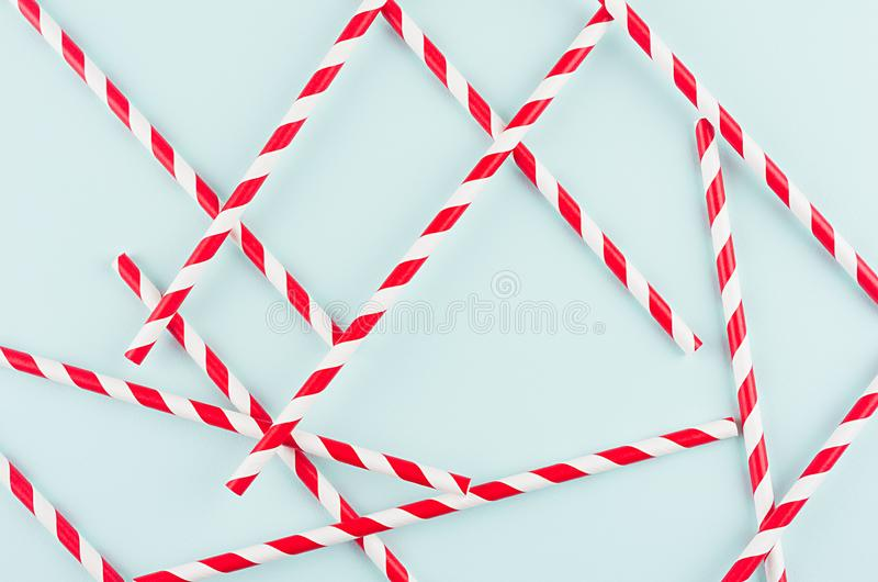 Playful trendy colors abstract background - red striped straws as pattern on mint paper backdrop. Playful trendy colors abstract background - red striped straws royalty free stock photo