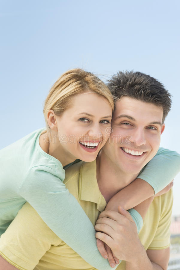 Playful Woman Embracing Man From Behind Against Clear Sky stock photo