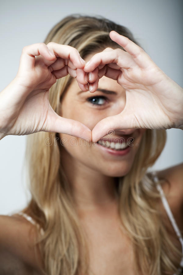 Playful woman making a heart gesture. Playful beautiful young blond woman making a heart gesture with her fingers to show her love and affection or that she royalty free stock images