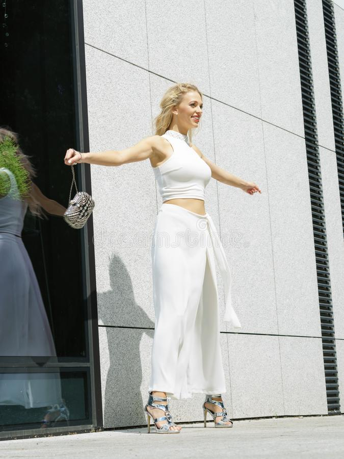 Playful woman wearing crop top and culottes. Elegant funny, playful fashionable woman presenting trendy urban outfit. White crop top and trousers culottes stock photos