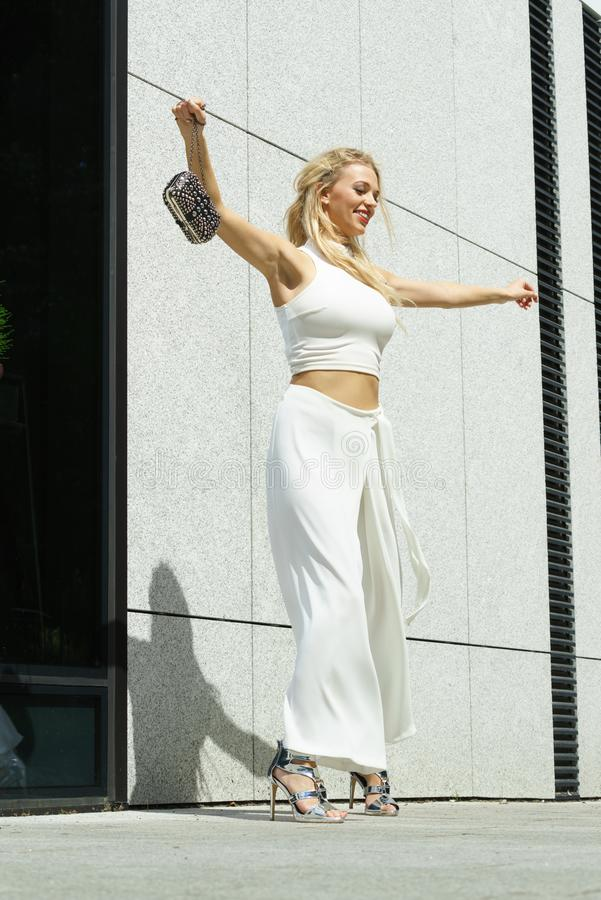 Playful woman wearing crop top and culottes. Elegant funny, playful fashionable woman presenting trendy urban outfit. White crop top and trousers culottes royalty free stock images