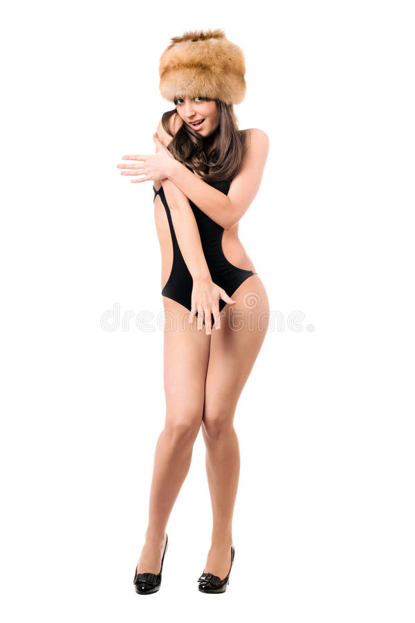 Playful woman wearing swimsuit and fur-cap. Playful woman wearing black swimsuit and fur-cap. Isolated on white stock photo