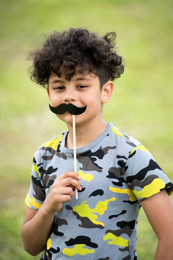 Playful young boy holding up a mustache stock photo