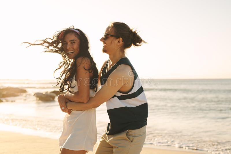 Playful young couple on beach vacation royalty free stock images