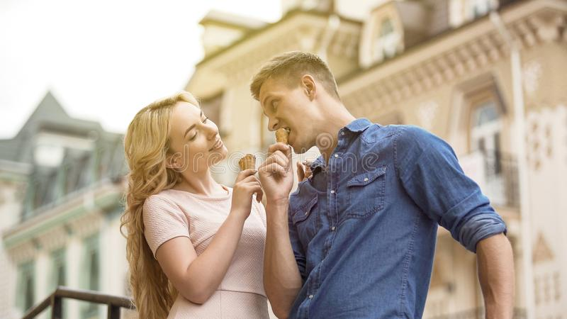 Playful young couple eating ice cream and flirting, sweet date in summer. Stock video royalty free stock image