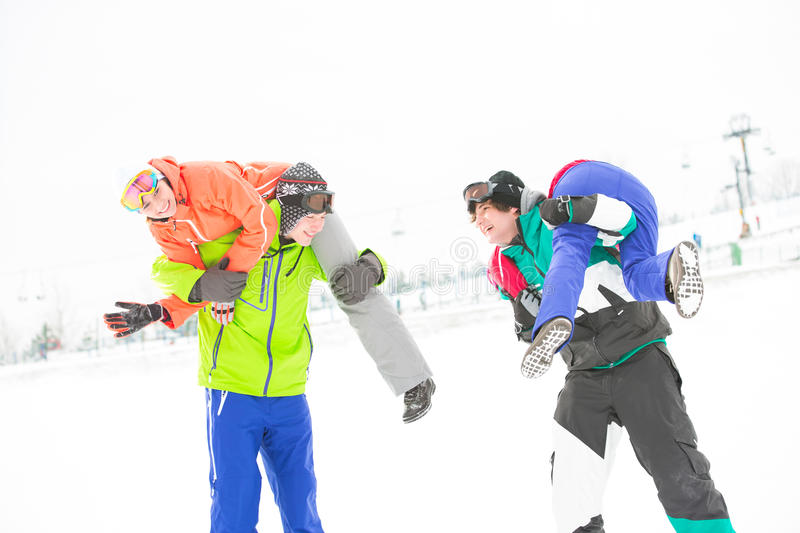Playful young couples enjoying in snow stock image
