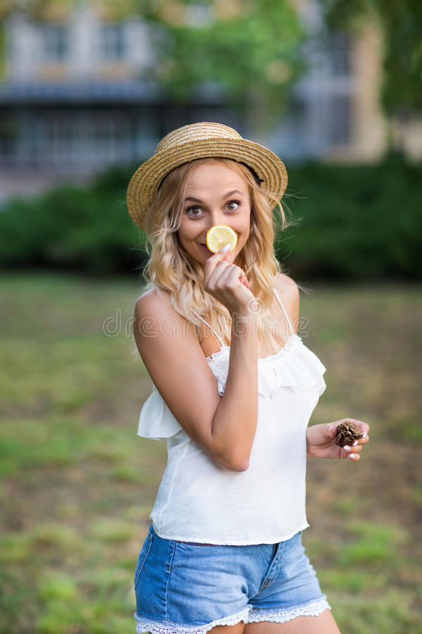 Playful young woman on a garden background. A joyful girl in a hat. Girl with a lemon. Exotic diets. Healthy lifestyle. royalty free stock photo