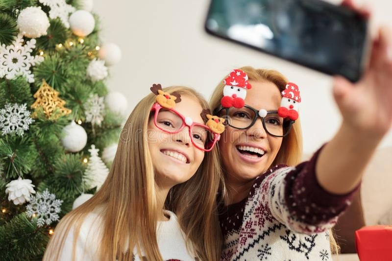 Playful young woman and teenage daughter posing and taking a selfie in front of a Christmas tree royalty free stock photography