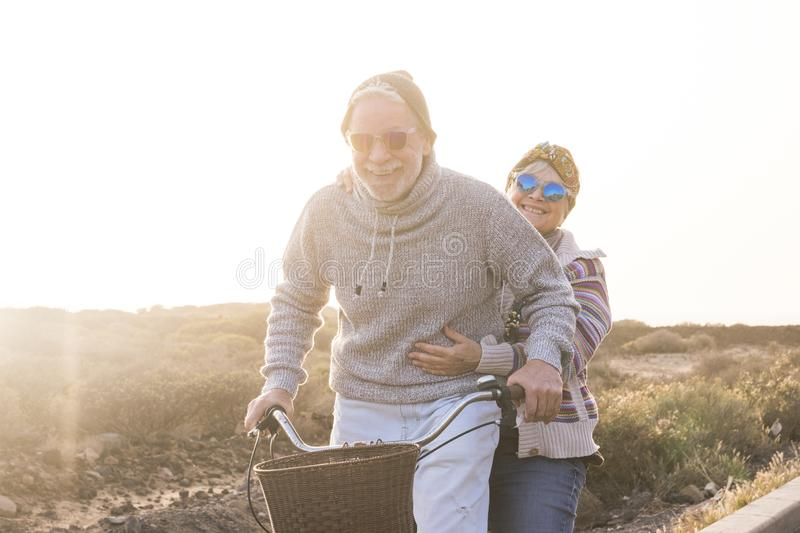 Playful and youthful senior caucasian peope couple enjoy a ride with bike together laughing and smiling -    concept of happiness stock photos