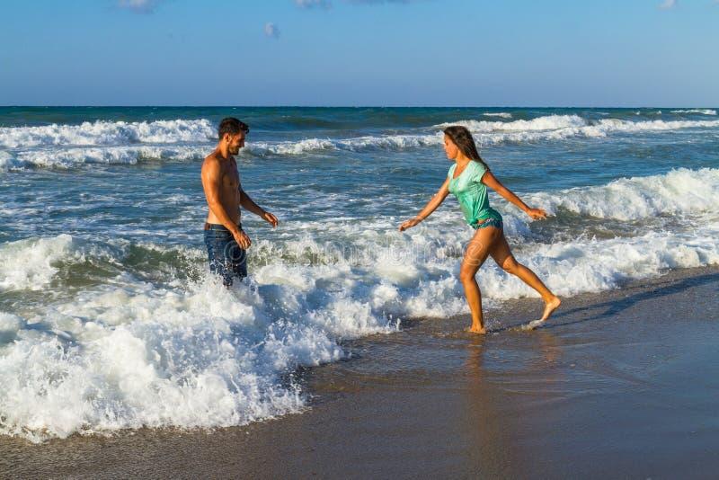 Playfull jong paar in bikini en borrels bij het strand stock foto's
