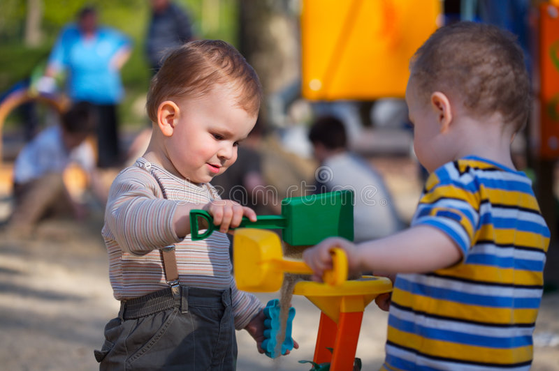 On the Playground. 2 years old children are playing together in the sandbox