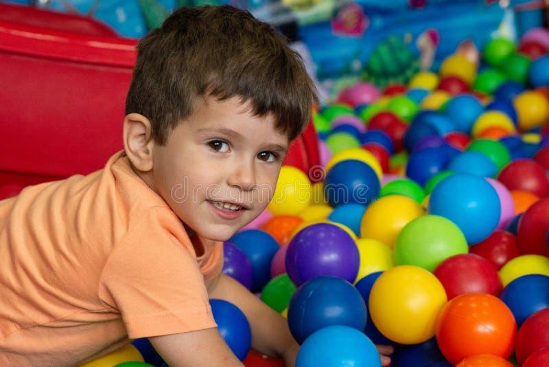Playground with ball pit indoor. Joyful kid having fun at indoor kids ball zone. stock image
