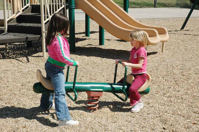 Playground Bully. Two little girls paly on a see-saw. One stands up to bully the other. Or could be used as it takes two to get things done. Friends in need royalty free stock images