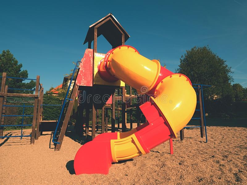 Playground colorful tube slide in public park. New slider tube and wooden ladders royalty free stock photography