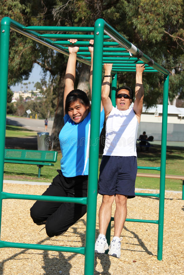 Playground Dad & Daughter. Father and his teenage daughter playing on the monkey bar at a playground