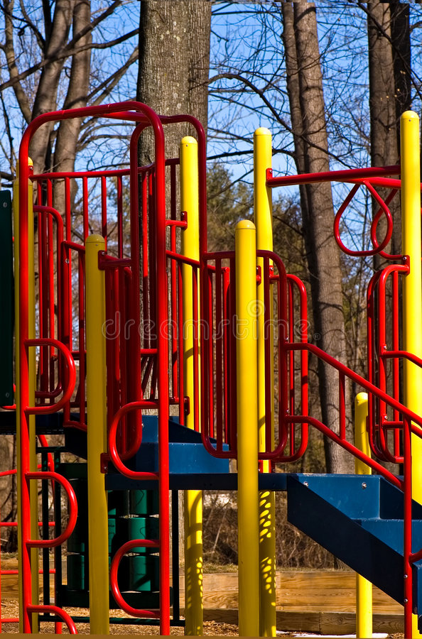 Playground Equipment. Colorful children's playground equipment in a park with a jungle gym to climb on during a sunny, late winter day stock image