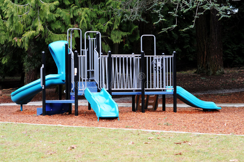 Playground equipment. Blue park playground equipment on a bed of wood chips at the edge of the woods stock images