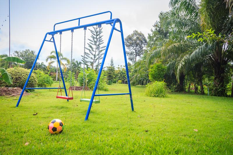 Playground equipment in the backyard for kids with soccer goal net and football on green grass field background. Playground equipment in the backyard for kids stock photos