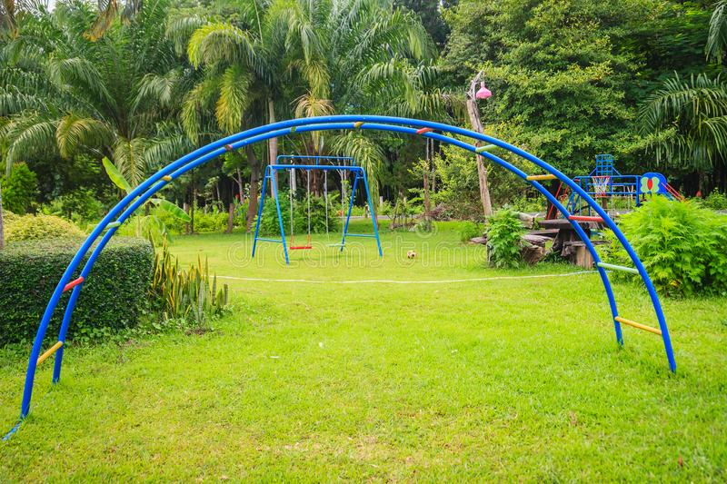 Playground equipment in the backyard for kids with soccer goal net and football on green grass field background. Playground equipment in the backyard for kids stock photography