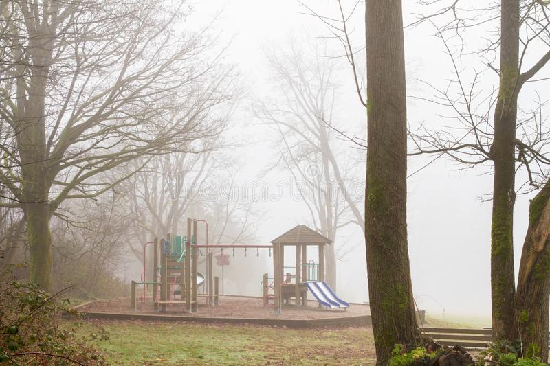 Playground equipment is unused on a damp and foggy morning; stock images