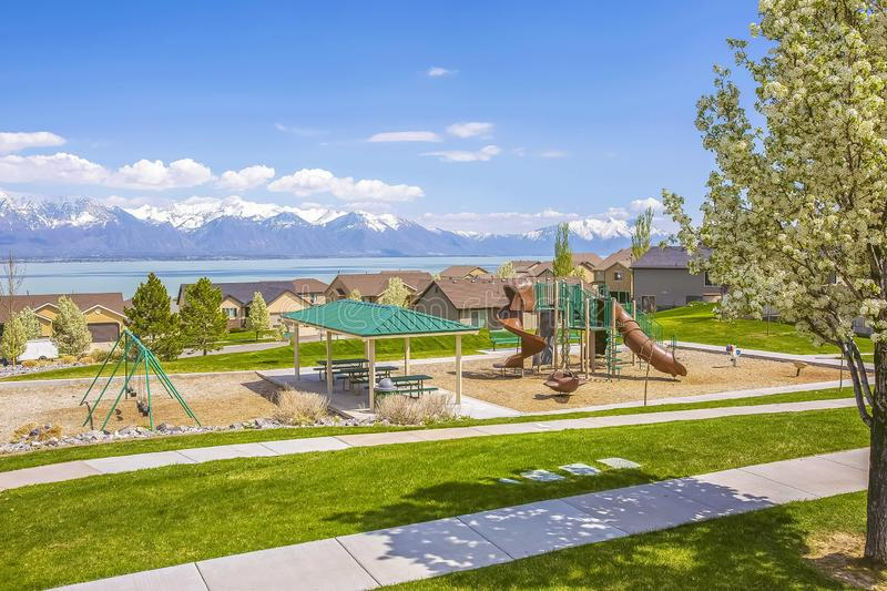 Playground and homes overlooking a lake and snowy mountain against blue sky. Grassy terrain with pathways and white flowering tree cna be seen in the royalty free stock image