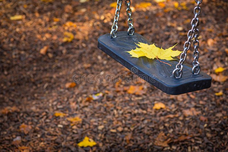Autumn, a lone leaf rests on a swing. royalty free stock image