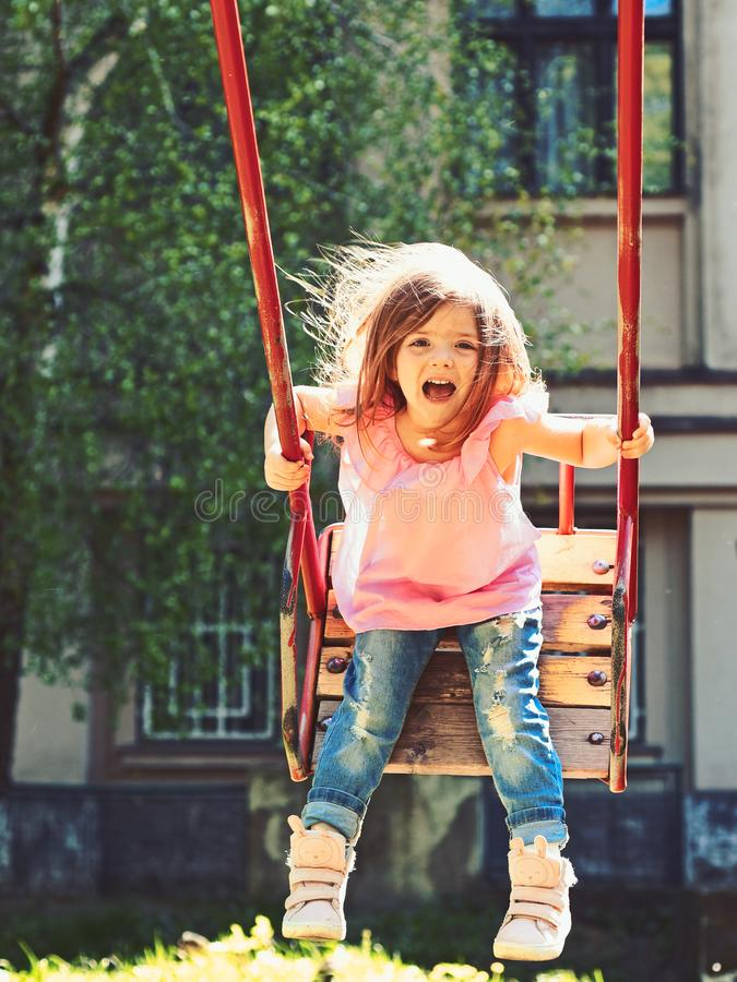 Playground in park. Small kid playing in summer. Happy laughing child girl on swing. romantic little girl on the swing stock image