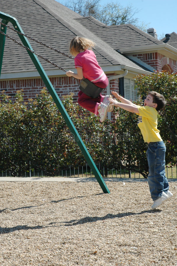 Playground Safety. Little boy jumps off the ground to catch little girl and give her a push. She is pushed sideways, causing a close call on the swings royalty free stock photos