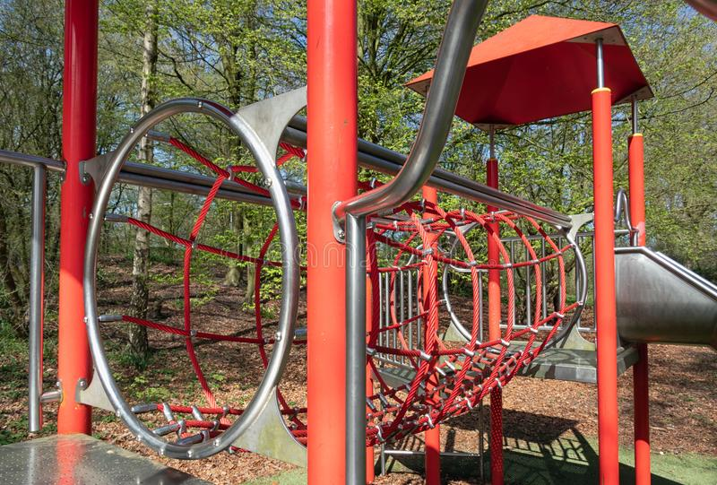 Playground with with slide in park Lelystad, The Netherlands. Playground with with rope tunnel and slide in city park Lelystad, The Netherlands royalty free stock images