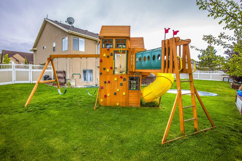 Playground structure with slide swings playhouse tower and climbing wall royalty free stock image