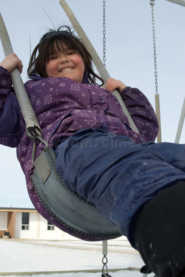 Playground Swing. A girl swinging on a playground swing in the middle of winter royalty free stock photography