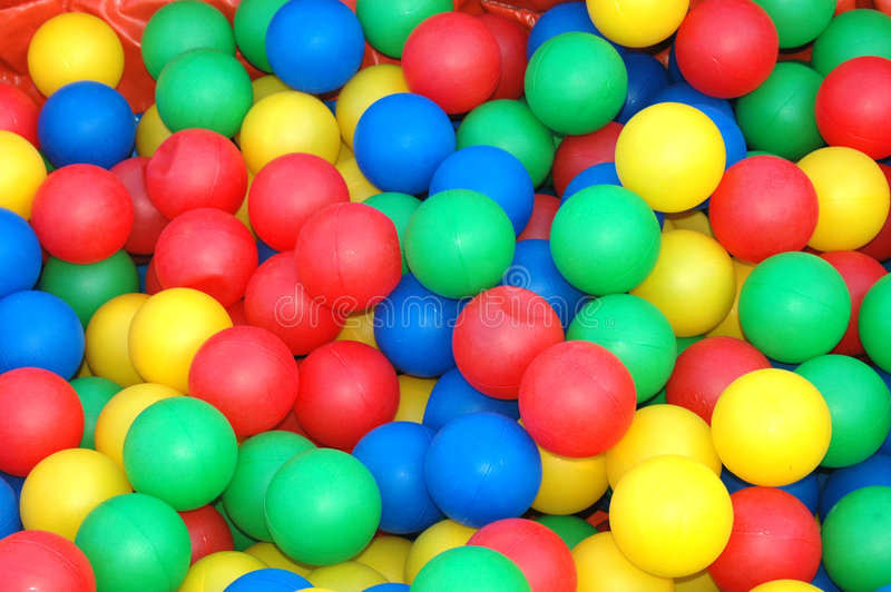 Playground toys. Background closeup of lots of colorful plastic balls in red, yellow, green and blue for kids to play with on the playground outdoors