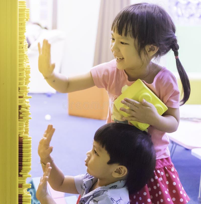 Playig asiatique d'enfants de mêmes parents sur le panneau d'aiguille photographie stock