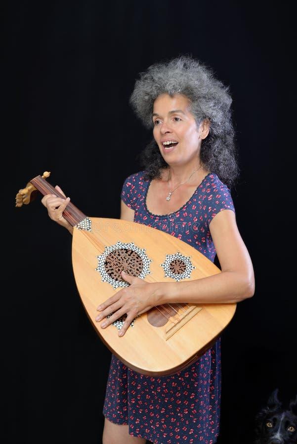 Playind Oud y canto de la mujer Perro en su lado imagenes de archivo