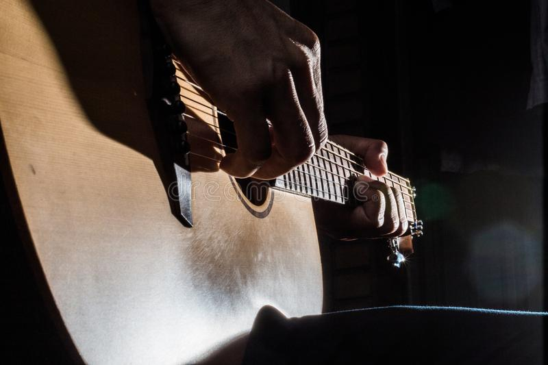 Playing acoustic guitar on low-key lighting background stock image