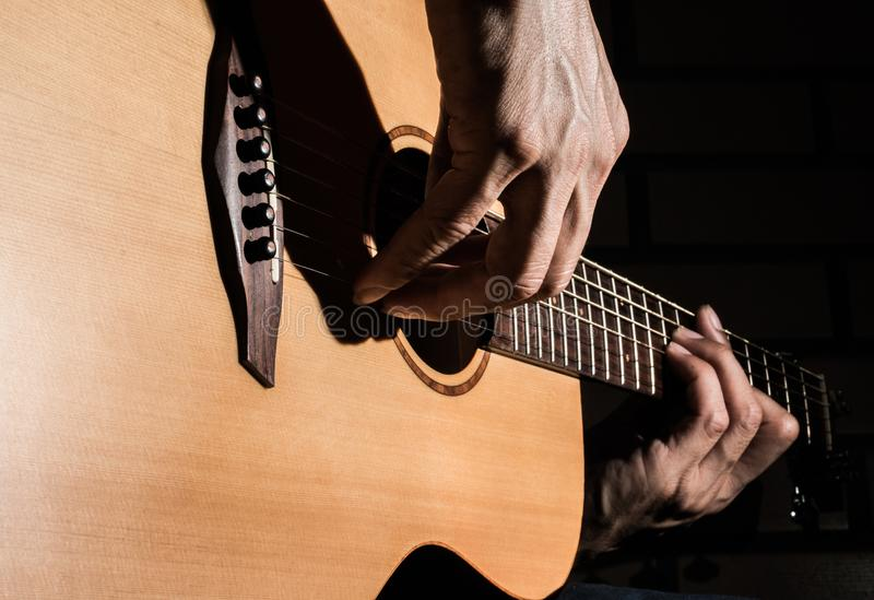 Playing acoustic guitar on low-key lighting background stock photography