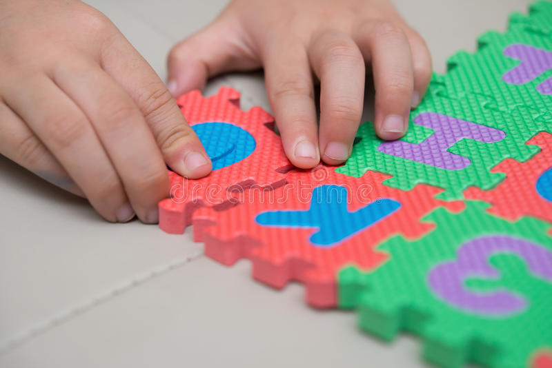 Playing alphabet jigsaw puzzles. Kid playing alphabet jigsaw puzzles stock photos