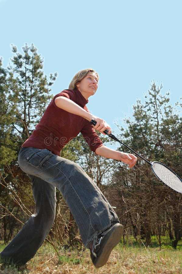 Playing badminton. Young pretty woman playing badminton outdoor royalty free stock image
