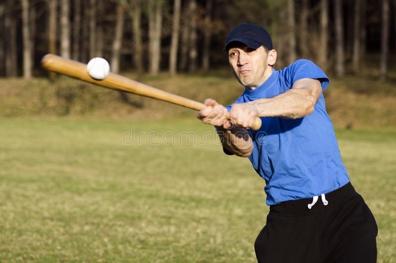 Playing baseball player. The baseball player is shooting the ball outdoors royalty free stock photo