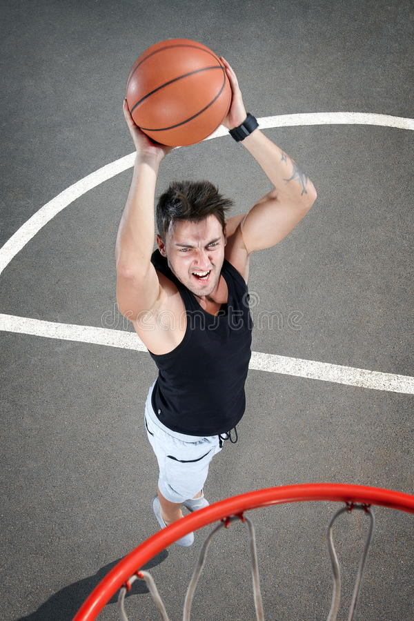 Playing basketball. Young man playing basketball game on concrete background royalty free stock images