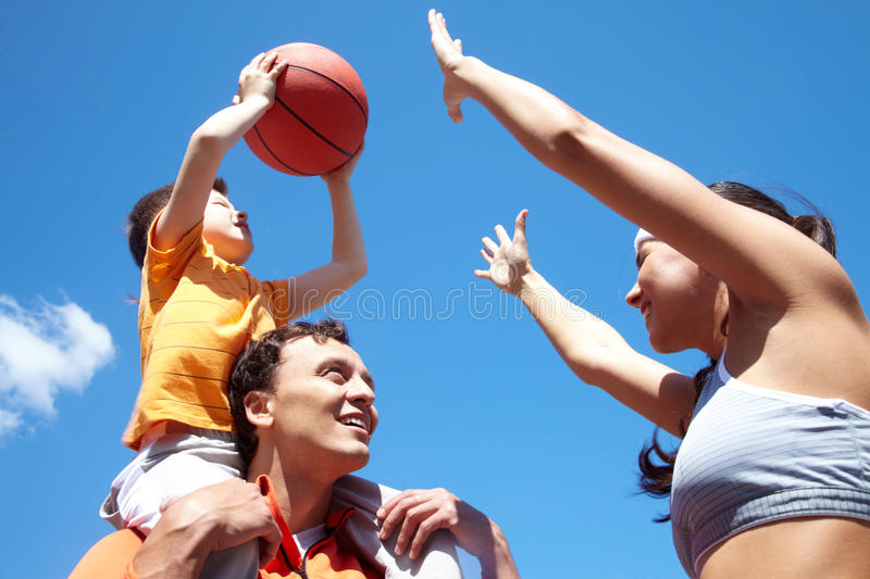 Playing basketball. Image of sporty couple and their son playing basketball royalty free stock image