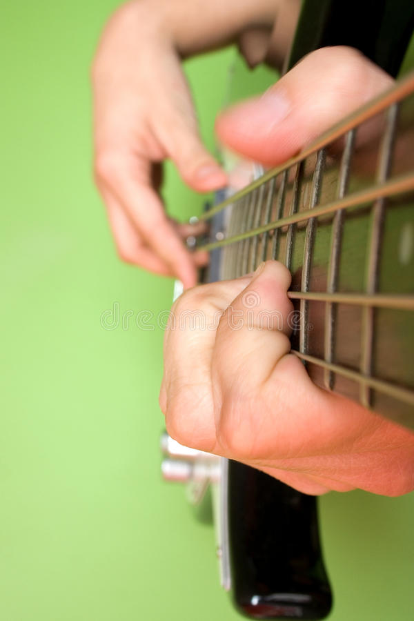 PLAYING THE BASS GUITAR. Fingers close-up playing the bass guitar royalty free stock photography