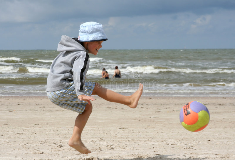 Playing at the Beach. A child playing with a ball at the beach royalty free stock photography