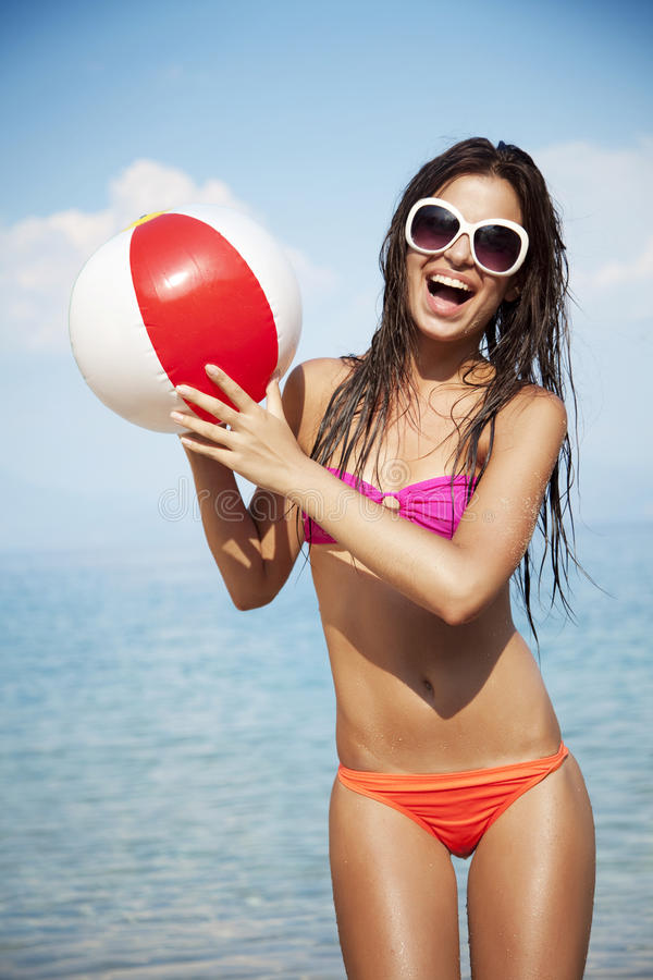 Playing beach ball. Young female at the beach playing ball royalty free stock photography