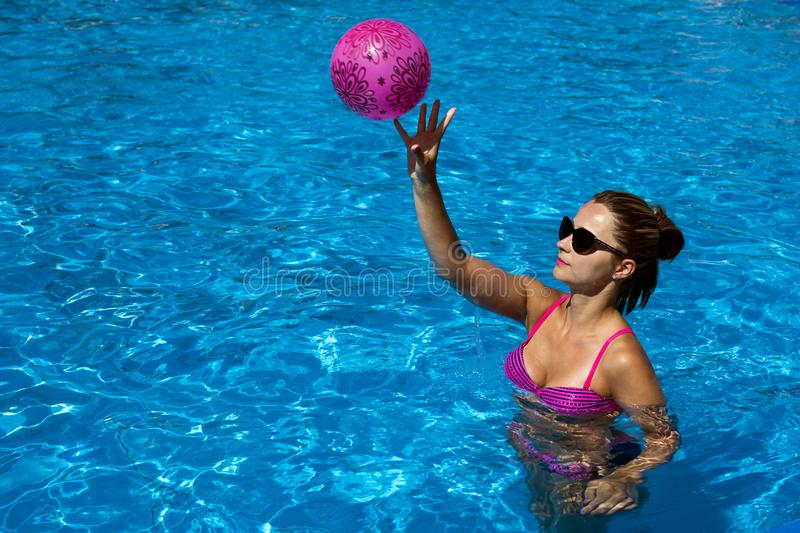 Playing beach ball in the swimming pool stock photos