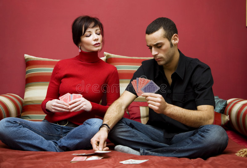 Playing cards. Young couple having fun playing cards at home royalty free stock images