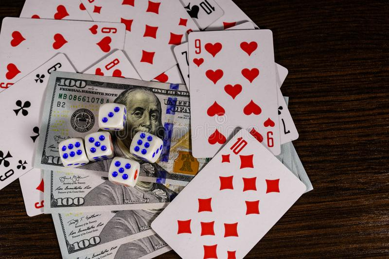 Playing cards, dice and one hundred dollar bills on a dark wooden table. Top view royalty free stock image