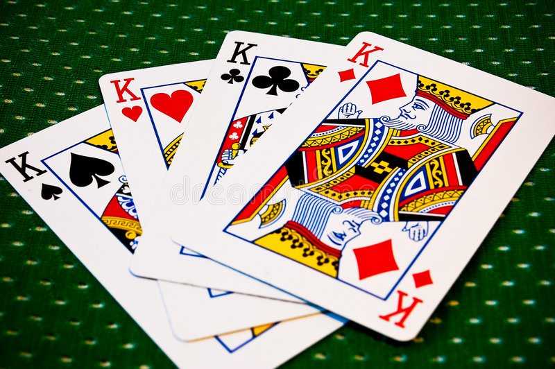 Playing Cards - Four Kings. A vibrant coloured image of four kings fanned out against a unique patterned tabletop stock images